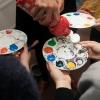 Juhendaja valab värvi lastekirjanduse keskuse kunstikambris